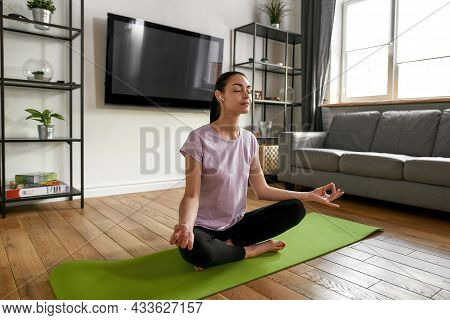 Mindful Young Woman In Sportswear Headphones In Lotus Asana Mudra Hands Have Meditation Session Prac
