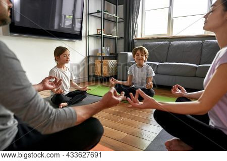 Happy Young Caucasian Parents With Children Sit In Lotus Pose With Mudra Hands Meditate Practice Yog