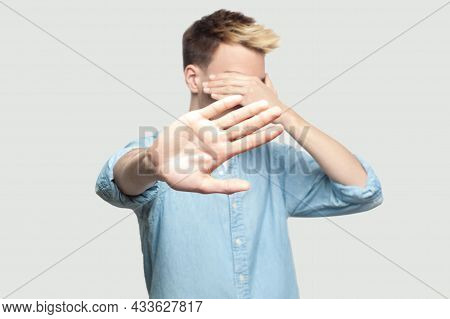 Stop, I Dont Want To See At This. Portrait Of Scared Handsome Young Man In Light Blue Shirt Standing