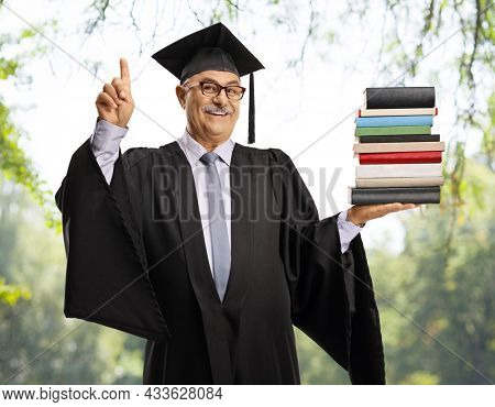 Happy mature man in a graduation gown holding a pile of books and pointing up, with trees in background