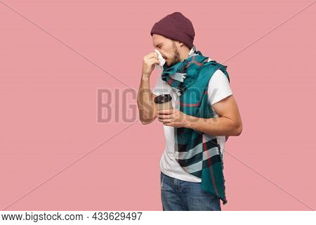 Portrait Of Sickness Modern Bearded Young Hipster Man In White Shirt And Casual Hat Standing, Sneeze