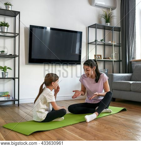 Vertical Narrow Shot Of Happy Active Young Caucasian Mother And Small Daughter Sit On Mats Workout H