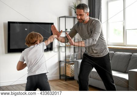 Loving Young Caucasian Father Train With Teen Small Son On Weekend Workout At Home. Caring Dad And L