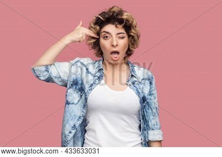 Portrait Of Crazy Young Woman With Curly Hairstyle In Casual Blue Shirt Standing With Pistol Hand Gu