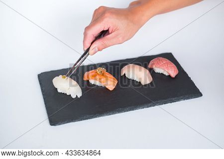 Sushi Nigiri Served On Black Tray. Four Sushi Pieces Served On Black Slate Isolated On The White Bac