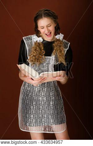 Amazed Teen Girl In School Uniform Reading Book. Pretty Surprised Graduate Teenage Girl With Braided