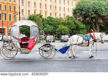 A Carriage On A City Street. Horse Harnessed To A Chariot. The Photo.