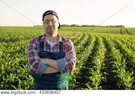 Middle Age Male Caucasian Confident Satisfied Farm Worker With Crossed Arms Stands At Corn Field