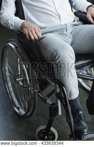 Partial View Of Disabled Businessman Sitting In Wheelchair In Office