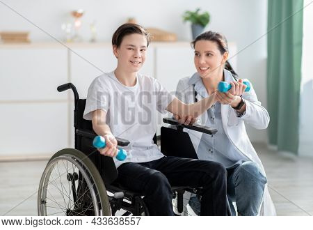 Female Physiotherapist Assisting Happy Teen Boy In Wheelchair To Do Exercises At Home. Physical Reha