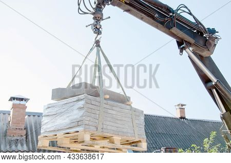 Unloading Paving Slabs From A Truck. Men Unload Paving Slabs Using A Manipulator. Workers Unload Bui