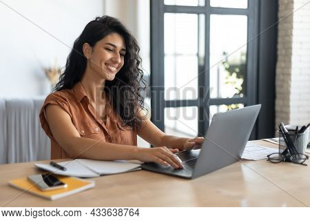 Freelance Job. Young Smiling Caucasian Woman Working On Laptop From Home, Sitting At Desk, Using Pc