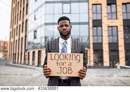 Young Black Businessman Holding Cardboard Sign With The Text Looking For A Job, Lost His Job Due To