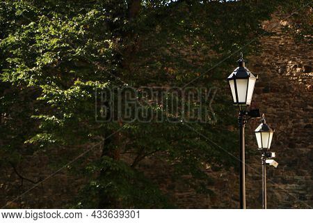 Old Lantern On A Background Of Blue Sky And Green Trees. Ancient Lantern On A Blue Background.