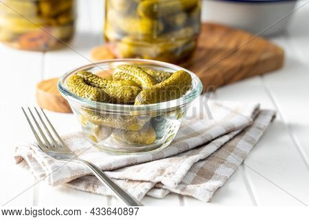 Small pickles. Marinated pickled cucumbers in bowl on checkered napkin.