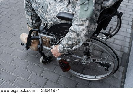 Partial View Of Handicapped Military Man Holding Bottle Of Alcohol While Sitting In Wheelchair Outdo