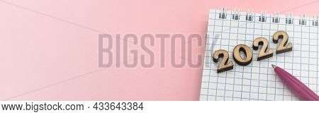 Wooden Numbers 2022. Notepad On A Spring. Notepad And Pen On Pink. Pink Pen. Spiral Spiral Checkered