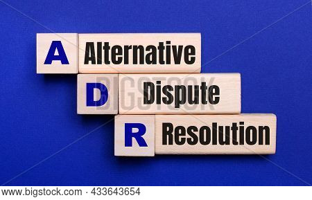 On A Bright Blue Background, Light Wooden Blocks And Cubes With The Text Adr Alternative Dispute Res