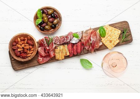 Antipasto board with prosciutto, salami, crackers, cheese, nuts, olives and rose wine. Top view with copy space