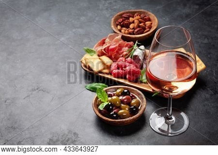 Antipasto board with prosciutto, salami, crackers, cheese, nuts, olives and rose wine. With copy space