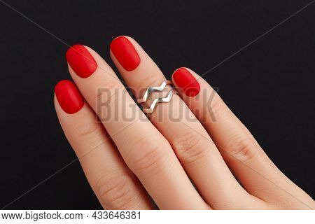 Close Up Womans Hand With Red Matt Nails On Black Background. Manicure, Pedicure Design Trends