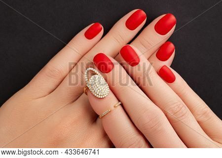 Close Up Womans Hands With Red Matt Nails On Black Background. Manicure, Pedicure Design Trends