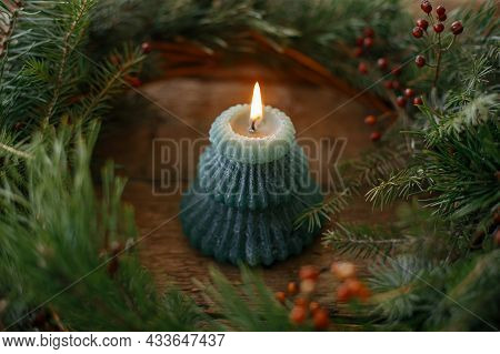 Christmas Advent. Stylish Burning Candle In Rustic Christmas Wreath On Old Wooden Background. Moody