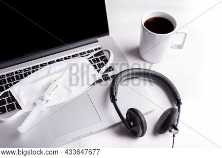 Face Mask And Syringe With Antivirus On The Computer Keyboard, Headset And A Cup Of Coffee