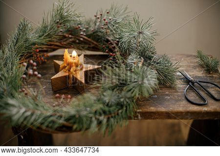 Stylish Burning Star Candle In Christmas Wreath With Spruce Branches And Berries On Rustic Wooden Ba