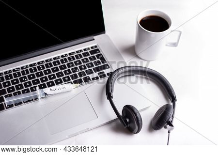 Syringe With Antivirus On The Computer Keyboard, Headset And A Cup Of Coffee