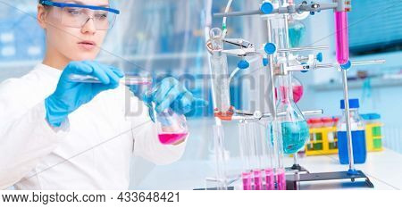 Attractive young female scientist working in laboratory.  Woman scientist looking at a red test tube in a lab. Young woman in chemical lab