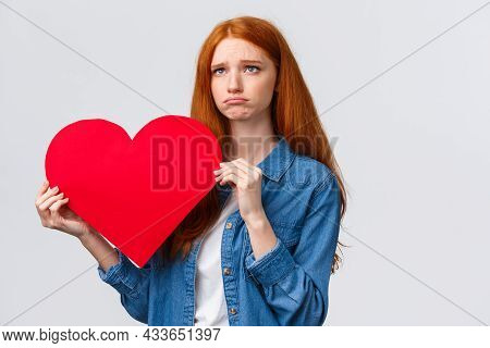 Unhapy Brokenhearted Cute Redhead Girl, Sulking And Looking Up Uneasy, Distressed Holding Big Red Va