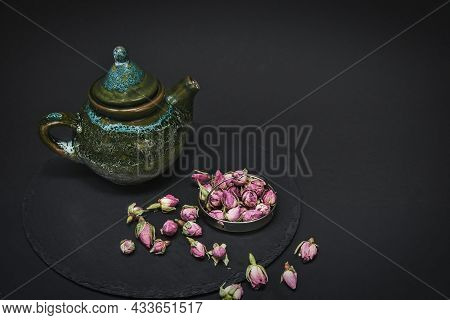 Dried Tea Rose Buds And Ceramic Vintage Teapot For Tea Ceremony In Chinese Style On Black Background
