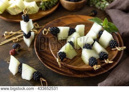 Festive Snack Of Fruit And Berry Canapes. Halloween Party Food. Canapes With Melon And Blackberries
