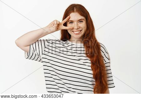 Happy And Positive Redhead Girl Showing Peace Sign Near Clean No Makeup Skin, V-sign Over Eye, Stand