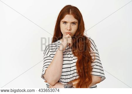 Image Of Thoughtful Redhead Teen Girl Squinting, Touching Chin, Consider Smth, Thinking, Making Deci