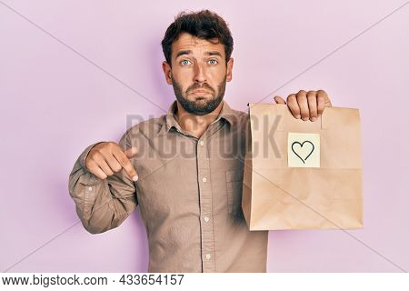 Handsome man with beard holding delivery paper bag with heart reminder pointing down looking sad and upset, indicating direction with fingers, unhappy and depressed.