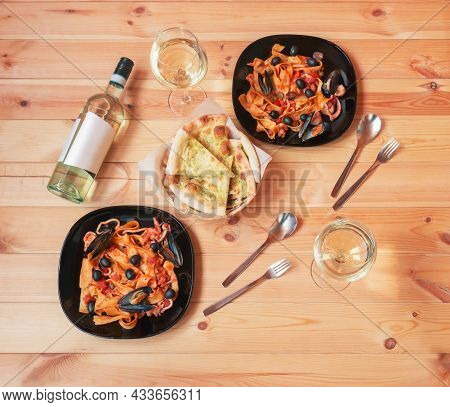 Plates Of Pappardelle Pasta With Seafood With Tomato Sauce, Bottle Of White Wine, Glasses Of White W