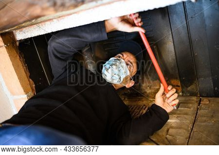 Young chimney sweep at work and wearing a mask to protect against coronavirus covid 19 pandemic