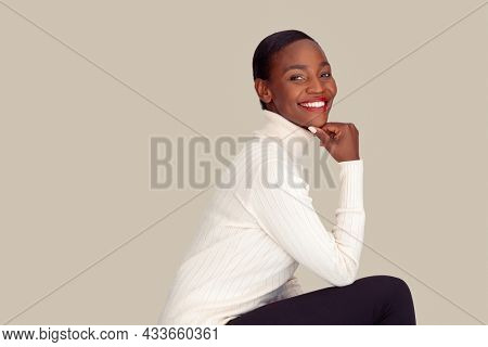 Beautiful woman wearing white sweater isolated on creamy background. Mid adult stylish woman sitting against light gray wall. Mature fashionable lady with turtle neck sweater smiling.