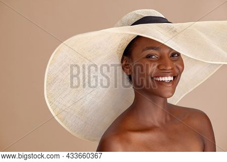 Beautiful mature woman with bare shoulder wearing summer hat with large brim and looking at camera. Portrait of smiling attractive black woman wearing straw hat with a wide brim isolated on background