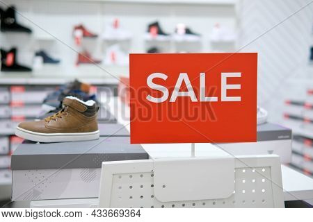 Sale sign notice into a clothes store. Shopping mall advertisement.