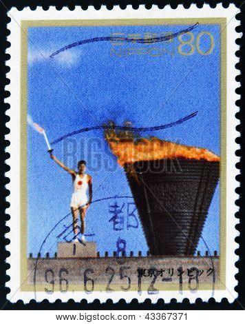 A stamp printed in Japan shows the lighting of the Olympic torch Yoshinori Sakai, Tokyo 1964