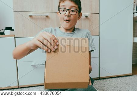 Excited Boy Sitting On A Carpet And Opening A Box, A Parcel, Unboxing And Unpacking Concept