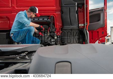 Professional Caucasian Truck Driver In His 30s Checking On Systems In His Semi Truck Before Next Lon