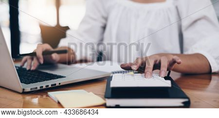 Business Woman Hand Using Laptop And Calculator. Account Or Saving Money Or Insurance Concept