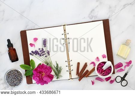 Natural skincare healing herbs and flowers for treating eczema, psoriasis and acne. Preparation of essential oil treatments with notebook. Health care herbal plant medicine concept. On marble.