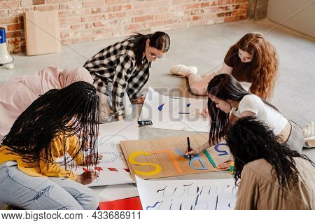 Multiracial young feminist women making posters during meeting indoors