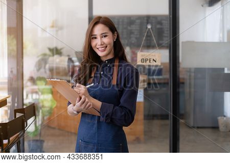 In The Background, A Successful Small Business Owner Stands In Front Of A Counter Preparing Coffee