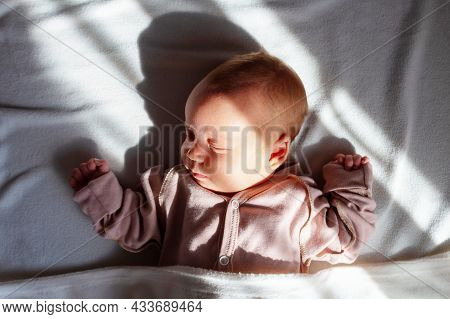 Adorable Caucasian Newborn Baby Girn In Pink Suit Sleeping In Her Bed On White Blanket. Morning Sunl